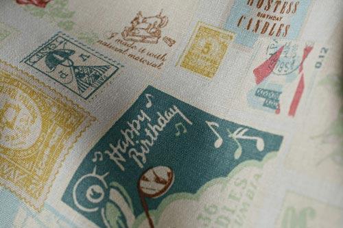 色々な切手がちりばめられた、ノスタルジックな綿麻生地